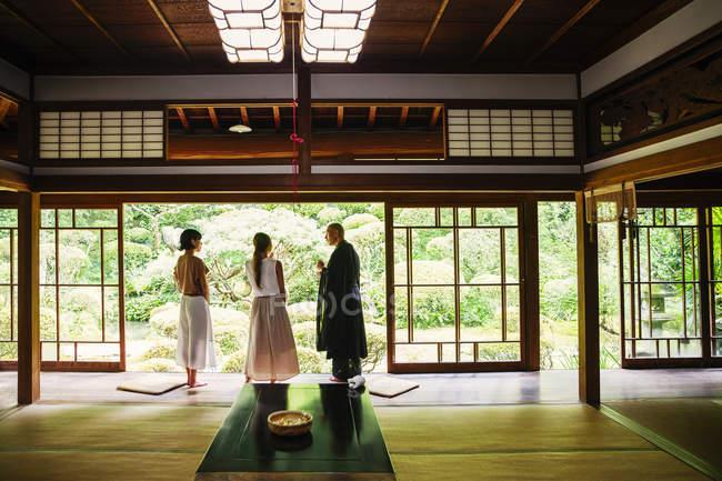 Буддийский священник и женщины, стоящие в буддийском храме . — стоковое фото