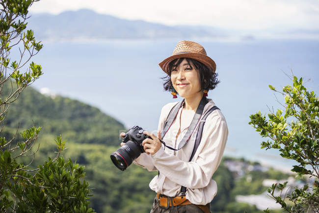 Japanese woman carrying backpack and holding camera standing on a cliff by ocean. — Stock Photo
