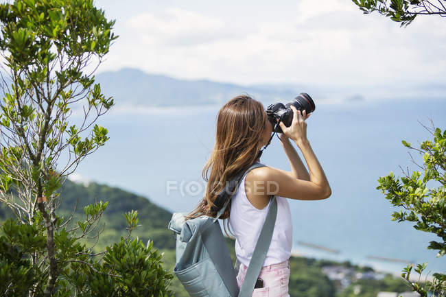 Donna giapponese che porta lo zaino scattare foto su una scogliera dall'oceano . — Foto stock
