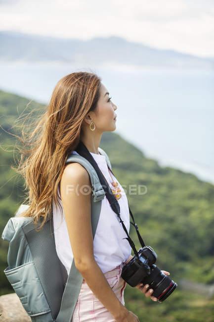 Japonesa mujer llevando mochila y sosteniendo cámara de pie en un acantilado por el océano . - foto de stock