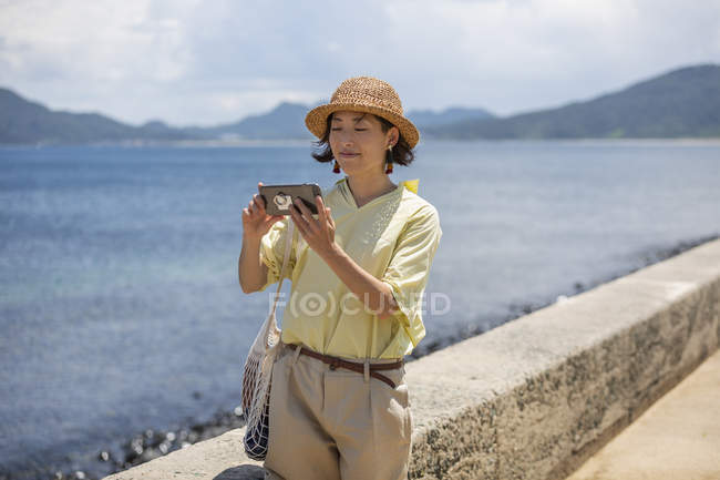 Japanese woman wearing hat standing by the ocean, taking picture with mobile phone. — Stock Photo