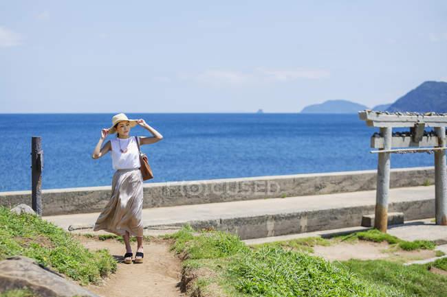 Femme japonaise portant un chapeau marchant le long du chemin par l'océan . — Photo de stock