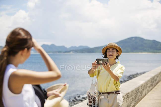 Две японки, стоящие у океана, фотографируются с помощью мобильного телефона . — стоковое фото