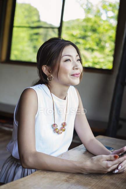 Femme japonaise souriante assise à une table dans un restaurant japonais . — Photo de stock