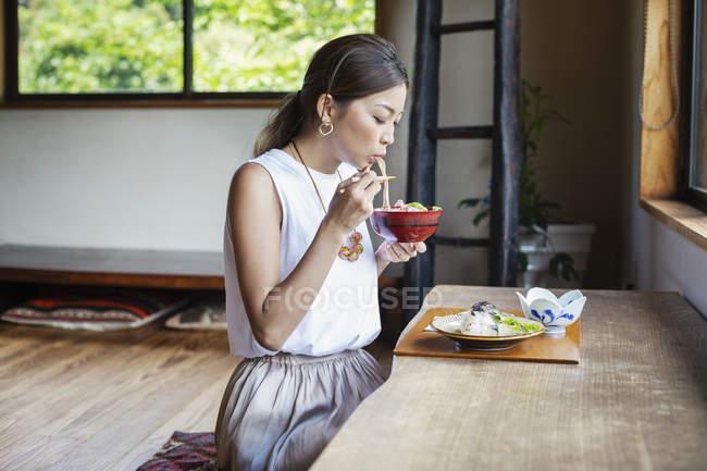 Femme japonaise assise à une table dans un restaurant japonais, mangeant . — Photo de stock