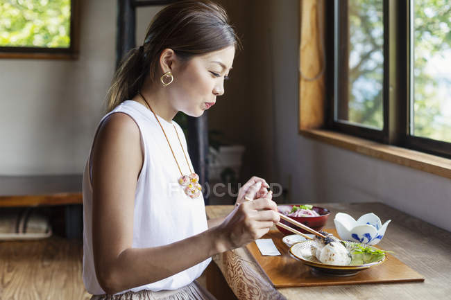 Japanese woman sitting at a table in a Japanese restaurant, eating. — Stock Photo