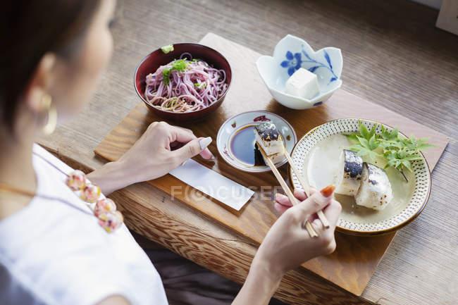 Vue en angle élevé de la femme japonaise assise à une table dans un restaurant japonais, mangeant . — Photo de stock
