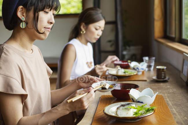 Две японки сидят за столом в японском ресторане, едят. — стоковое фото