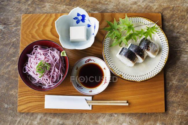Високий кут, зблизька суші, тофу, локшини і соєвий соус на столі в японському ресторані.. — стокове фото