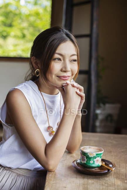 Femme japonaise souriante assise à table dans un restaurant japonais . — Photo de stock