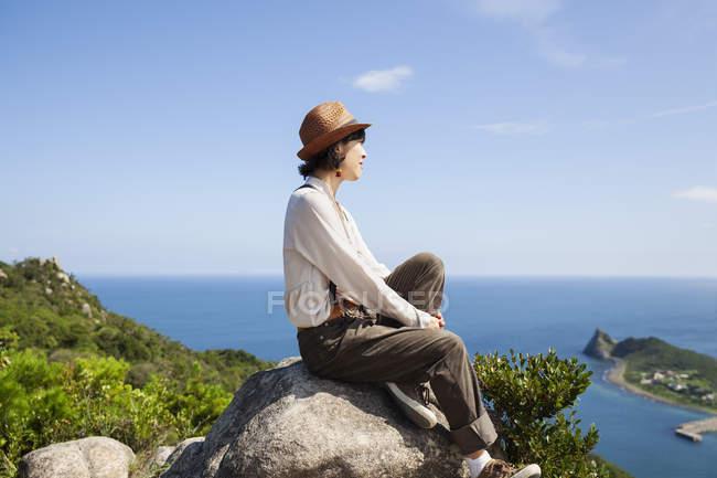 Giapponese donna indossare cappello seduta su un rocce su scogliera con oceano scenario . — Foto stock