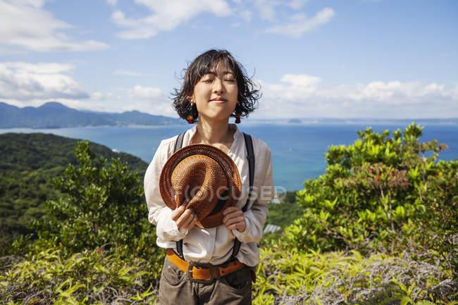 Mulher japonesa segurando chapéu de pé em um penhasco com paisagem oceânica. — Fotografia de Stock