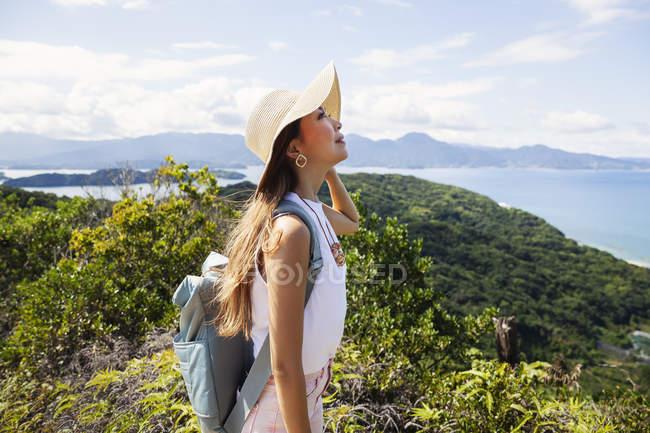 Femme japonaise portant chapeau et sac à dos debout sur une falaise avec des paysages océaniques . — Photo de stock
