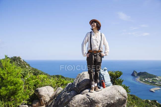 Giapponese donna indossare cappello in piedi su una roccia sulla scogliera con oceano scenario . — Foto stock