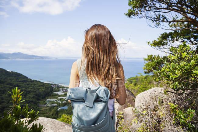 Vista posteriore della donna che porta lo zaino in piedi su una roccia sulla scogliera con paesaggio oceanico . — Foto stock