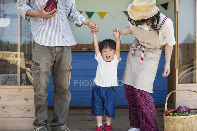 Japanese man, woman and boy standing outside a farm shop, holding hands. — Stock Photo