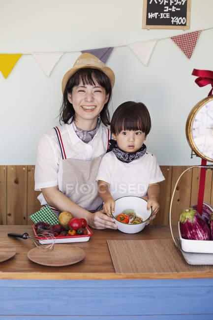 Японская женщина и мальчик стоят в фермерском магазине, готовят еду . — стоковое фото
