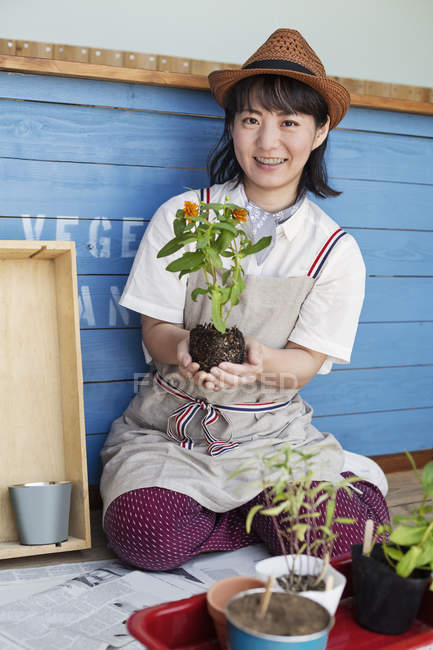 Japanese woman sitting outside a farm shop, planting flowers into flower pots. — Stock Photo