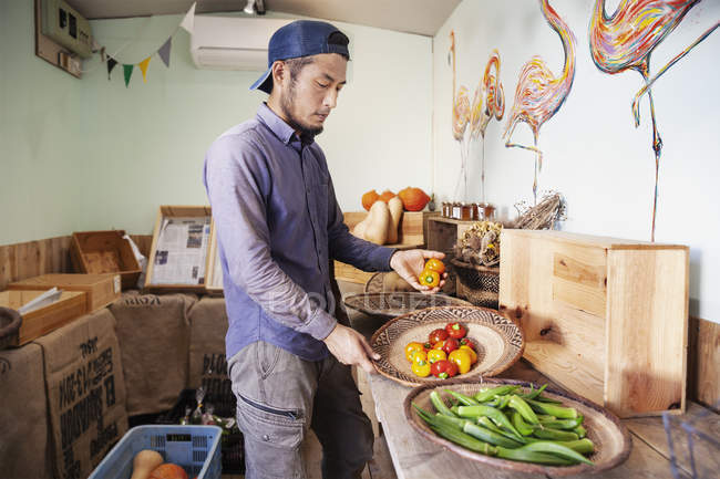 Japanese man wearing cap standing in farm shop, holding bowls with fresh vegetables. — Stock Photo
