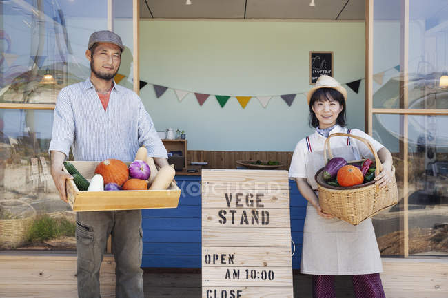 Japanese man and woman standing outside a farm shop, holding crate and basket with fresh vegetables, looking in camera. — Stock Photo