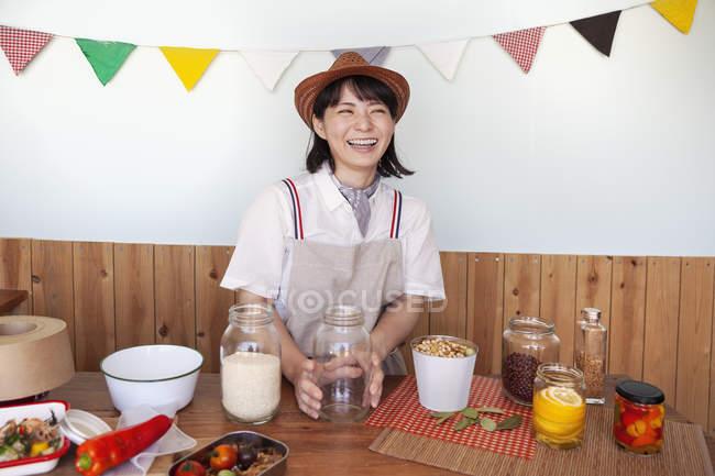 Mulher japonesa usando chapéu de pé em uma loja de fazenda com uma seleção de alimentos e condimentos em frascos de vidro . — Fotografia de Stock