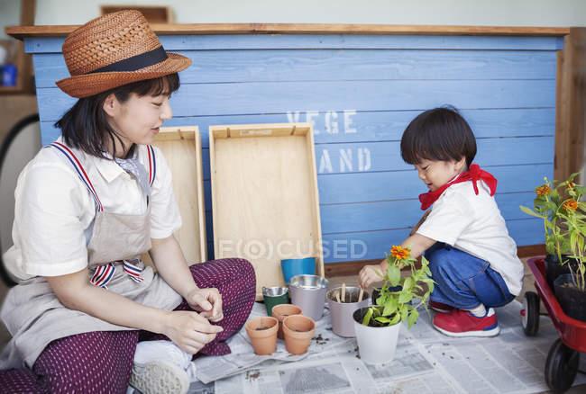Femme japonaise portant chapeau et garçon assis devant un magasin de ferme, plantant des fleurs dans des pots de fleurs . — Photo de stock