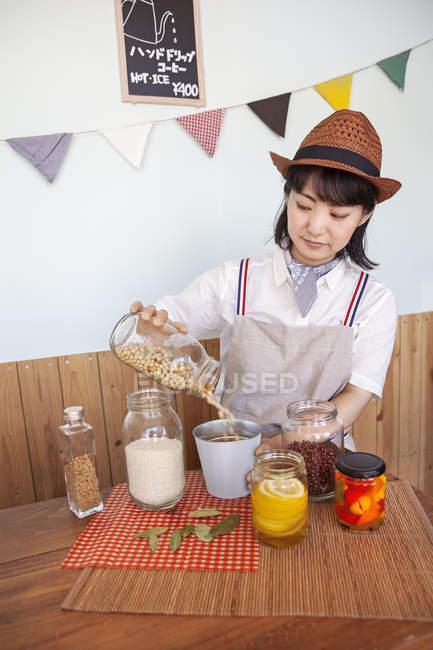 Mujer japonesa que lleva sombrero en una tienda de campaña con una selección de alimentos y condimentos en tarros de vidrio.. - foto de stock