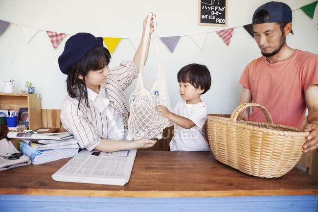 Japanese man, woman and boy standing in a farm shop, sorting clear plastic bottles into basket. — Stock Photo