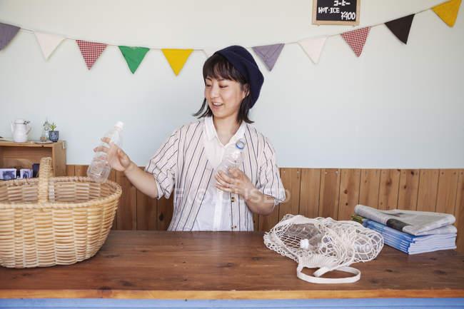 Японка, стоя в фермерском магазине, складывает пластиковые бутылки в корзину. — стоковое фото
