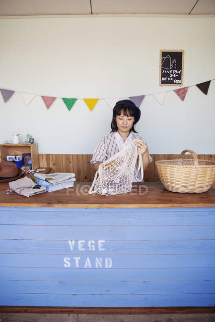 Japanese woman standing in a farm shop, sorting clear plastic bottles into net bag and basket. — Stock Photo