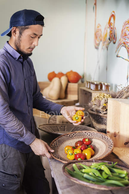 Japanese man wearing cap standing in farm shop, holding bowl with fresh vegetables. — стокове фото