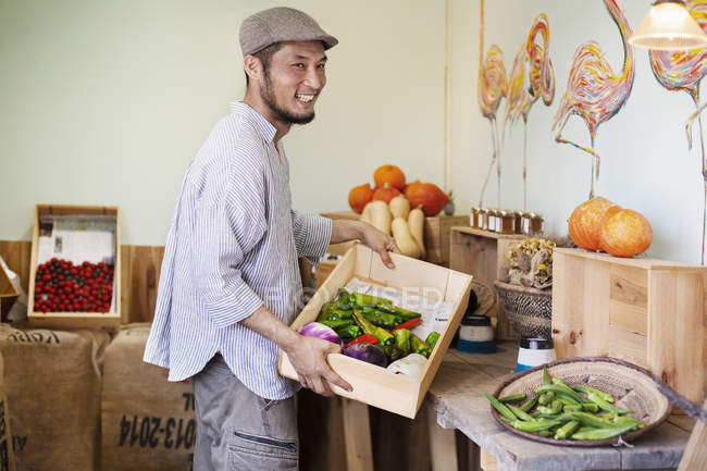Smiling Japanese man wearing cap standing in farm shop, holding crate with fresh vegetables. — Stock Photo