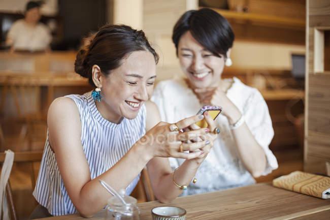 Zwei japanische Frauen sitzen an einem Tisch in einem vegetarischen Café und benutzen ein Mobiltelefon. — Stockfoto