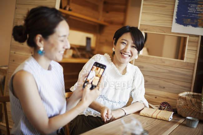 Zwei japanische Frauen, die an einem Tisch in einem vegetarischen Café sitzen, ihr Handy benutzen und Fotos machen. — Stockfoto