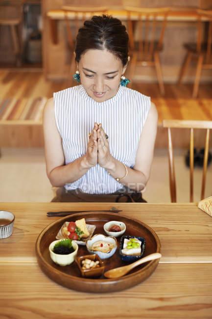Высокий угол обзора японской женщины, сидящей перед выбором вегетарианской еды в кафе, готовой к еде . — стоковое фото