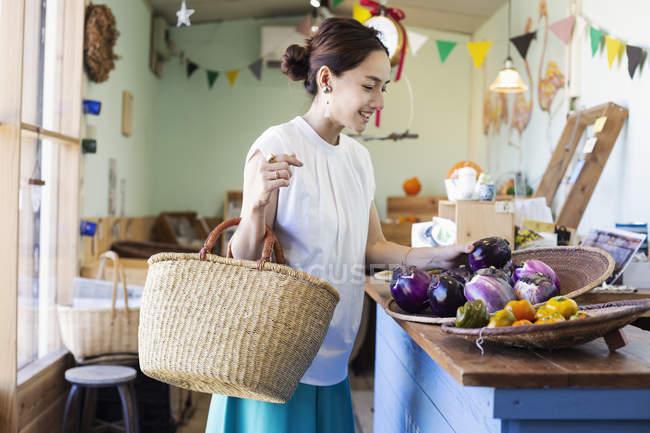Japanese woman shopping fresh aubergines in a farm shop. — Stock Photo