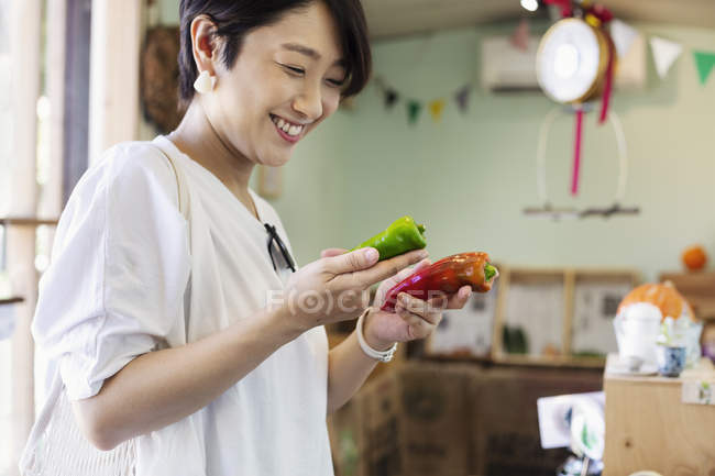 Smiling Japanese woman standing in a farm shop, holding organic peppers. — Stock Photo