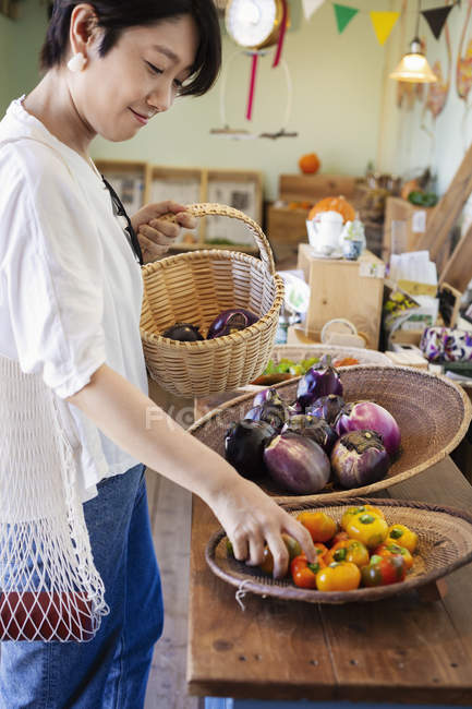 Japanese woman shopping fresh peppers in a farm shop. — Stock Photo