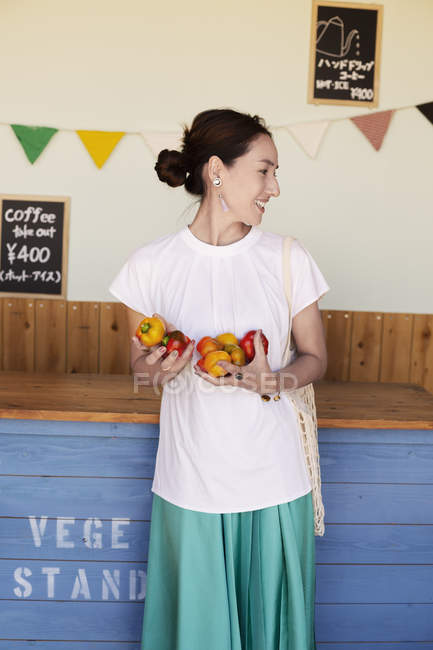 Smiling Japanese woman standing in a farm shop, holding vegetables. — Stock Photo