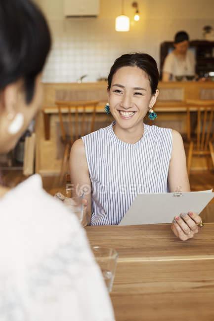 Lächelnde Japanerin sitzt mit Freundin an einem Tisch in einem vegetarischen Café und hält Menü. — Stockfoto