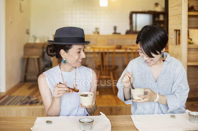 Zwei lächelnde Japanerinnen beim Essen in einem vegetarischen Café. — Stockfoto