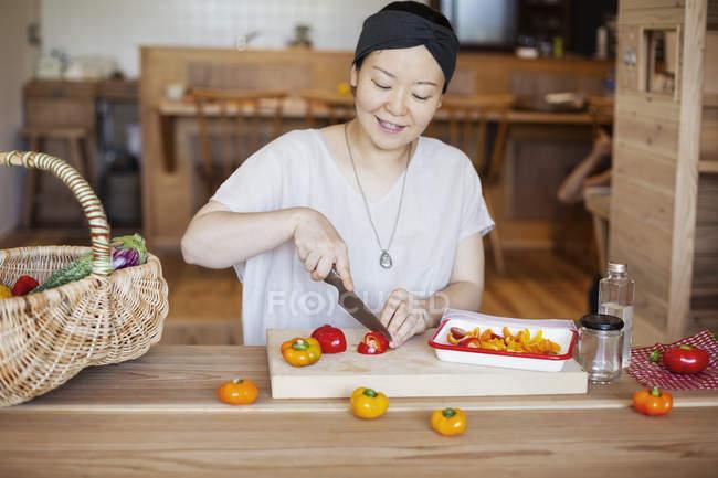 Japanese woman preparing fresh vegetables in a vegetarian cafe. — Stock Photo