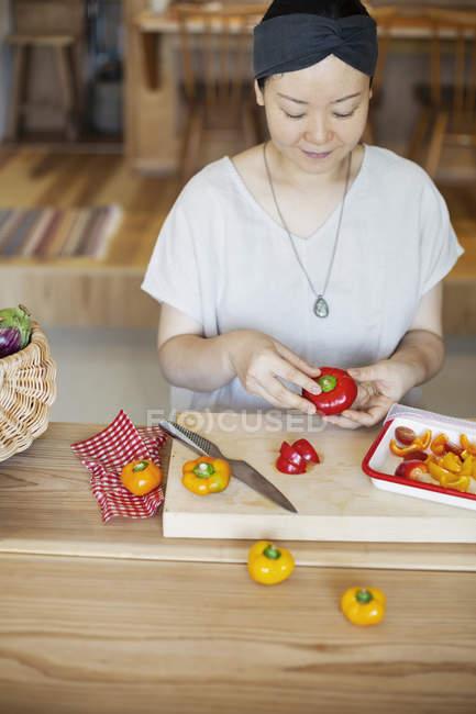 Mujer japonesa preparando verduras frescas en un café vegetariano . - foto de stock