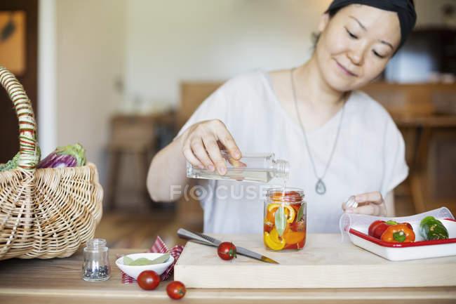 Japanese woman preparing preserved vegetables in jar in a vegetarian cafe. — Stock Photo