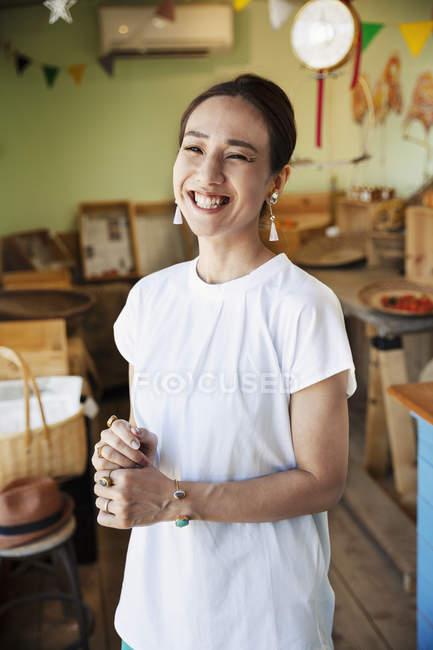 Посміхаючись, японська жінка стоїть у фермерському магазині і дивиться в камеру.. — стокове фото