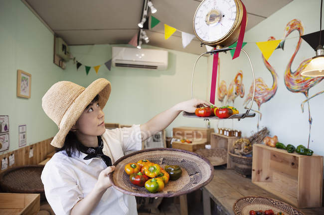 Japanese woman in hat working in a farm shop, weighing fresh peppers. — Stock Photo