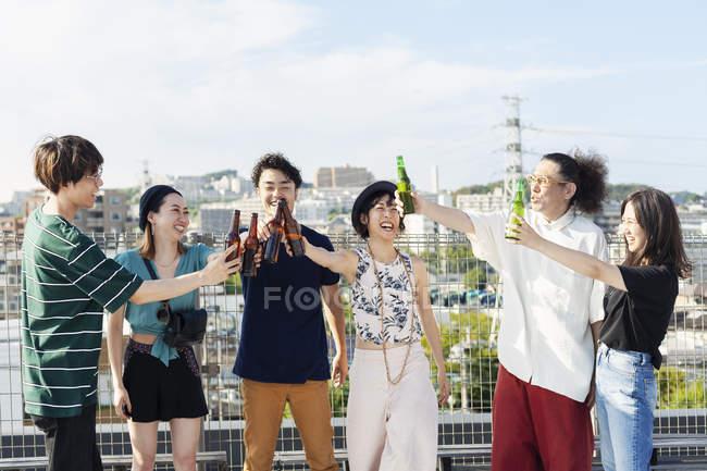 Группа молодых японских мужчин и женщин, стоящих на крыше в городской обстановке, пьющих пиво. — стоковое фото