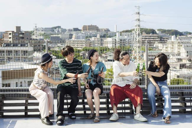 Группа молодых японских мужчин и женщин, сидящих на крыше в городской обстановке, пьющих пиво . — стоковое фото