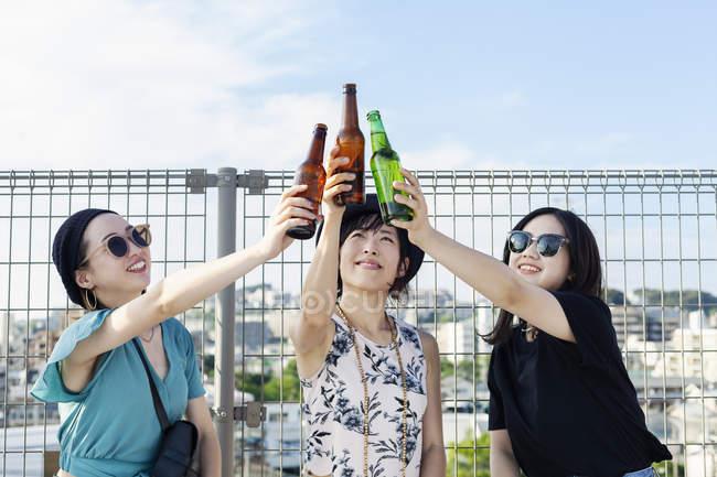 Giovani donne giapponesi sedute sul tetto in ambiente urbano, brindando alla birra . — Foto stock