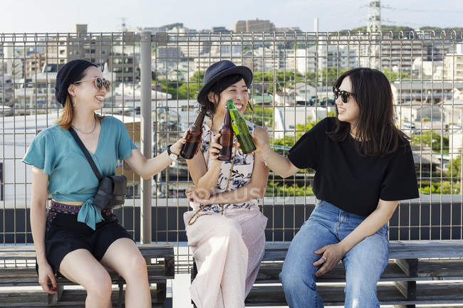 Three young Japanese women sitting on rooftop in urban setting, drinking beer. — Stock Photo